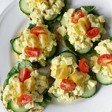 Egg free egg mayo on rice cakes pictured from above served with spinach and baby heritage tomatoes