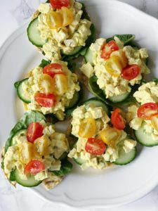 Egg free egg mayo on Rude Health chickpea & lentil crackers with spinach, cucumber & tomato, pictured from above